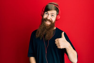 Naklejka Redhead man with long beard listening to music using headphones doing happy thumbs up gesture with hand. approving expression looking at the camera showing success.