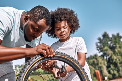 Naklejka Responsible father fixing a flat tyre of his son bike