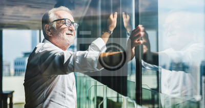 Naklejka Retirement concept. Senior grey-haired businessman standing and looking to right hand at modern business lounge high up in an office tower.
