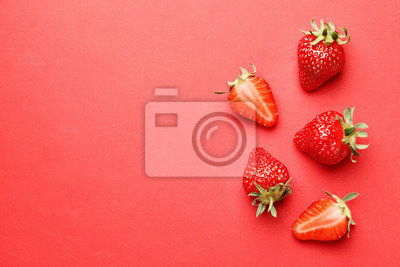 Naklejka Ripe juicy strawberries on a red background. pattern. Creative summer background composition with strawberry. Minimal fruit concept.