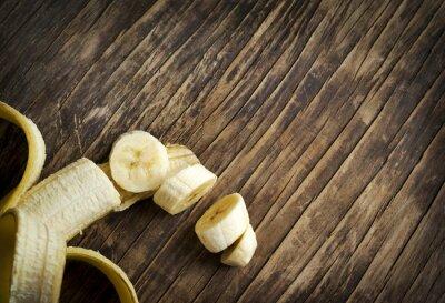 Naklejka Ripe sliced banana on wooden background