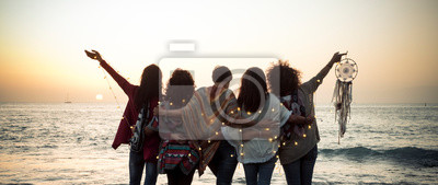 Naklejka Romance and emotion concept with group of people women friends viewed from back hugging and ejoying the sunset in outdoor nature sea vacation concept - friendship and freedom for travelers