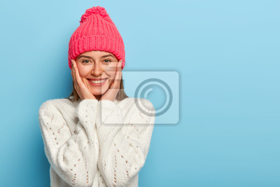 Naklejka Romantic positive young European woman smiles gently, has white perfect teeth, touches both cheeks, has friendly look, wears pink hat with pompon and white sweater, models against blue wall.
