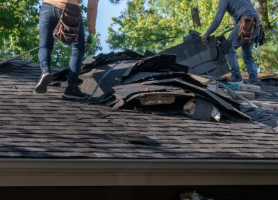 Naklejka Roofers removing old material from a house in preparation for storm damage repair.