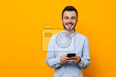 Naklejka Rozochocony młody człowiek w przypadkowym używa telefonie nad żółtym tłem