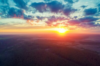 Rural landscape in the morning with a beautiful burning sky. Bird's-eye. Panoramic view of pine forest, fields, river and village during bright sunrise