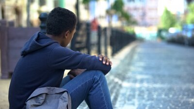 Naklejka Sad mixed-race teenager sitting on sidewalk, relationship problems, awkward age