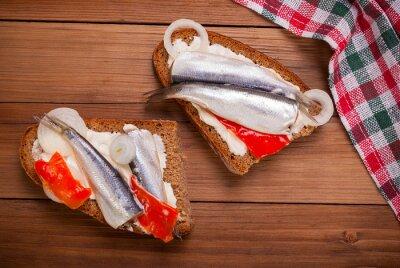 Naklejka Sandwich z szprota na drewnianym tle.