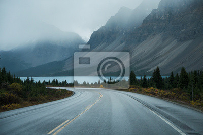 Naklejka Scenic road trip with rocky mountain and lake in gloomy day