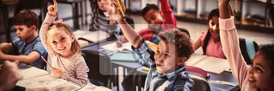 Naklejka Schoolkids raising their hands in classroom