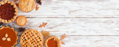 Naklejka Selection of homemade autumn pies. Pumpkin, apple and pecan. Above view corner border on a white wood background with copy space.