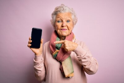 Naklejka Senior beautiful grey-haired woman holding smartphone showing screen over pink background very happy pointing with hand and finger