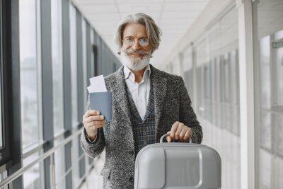 Naklejka Senior businessman with travel suitcase in airport