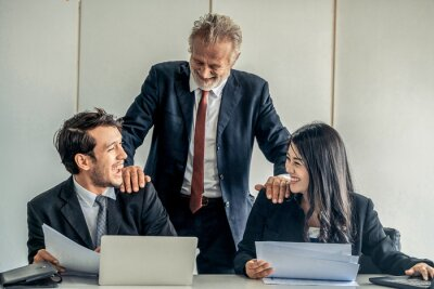 Naklejka Senior caucasian manager working in office with assistance of young Asian business people and translator in the meeting. Corporate international business and secretary language translation concept.