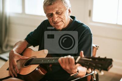 Naklejka Senior man playing on his guitar
