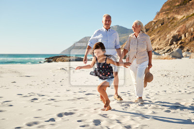 Naklejka Senior white couple and their granddaughter walking on a sunny beach, close up