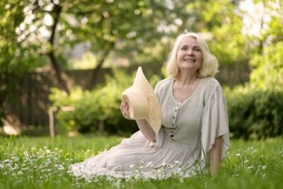 Naklejka Senior woman in dress sitting on grass at the park