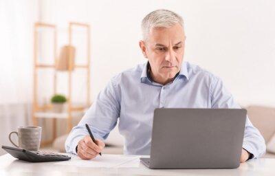 Naklejka Serious senior man using laptop and writing