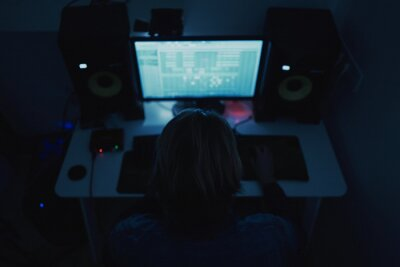 Naklejka Shallow focus of an adult producer composing music with a computer in a dark room