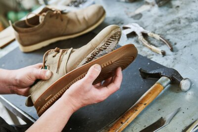 Naklejka Shoemaker repair shoe. Glueing the sole for male footwear