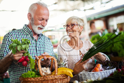 Naklejka Shopping, food, sale, consumerism and people concept - happy senior couple buying fresh food