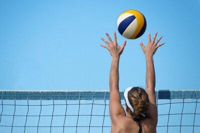 Naklejka Siatkówka plażowa graczem skoki w sieci i stara się bloków piłkę