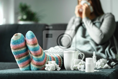 Naklejka Sick woman with flu, cold, fever and cough sitting on couch at home. Ill person blowing nose and sneezing with tissue and handkerchief. Woolen socks and medicine. Infection in winter. Resting on sofa.