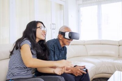 Naklejka Side portrait of beautiful Asian woman sitting on a sofa with her old father, while guiding him how to play vr glasses in their living room