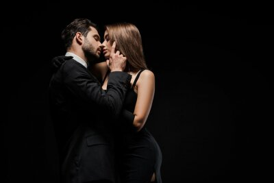 Naklejka side view of handsome man touching face of attractive woman in dress isolated on black