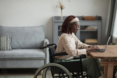 Naklejka Side view portrait of young African-American woman using wheelchair while working from home in minimal grey interior, copy space