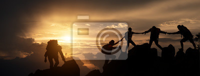 Naklejka Silhouette of Hikers climbing up mountain cliff. Climbing group helping each other while climbing up in sunset. Concept of help and teamwork, Limits of life and Hiking success full.