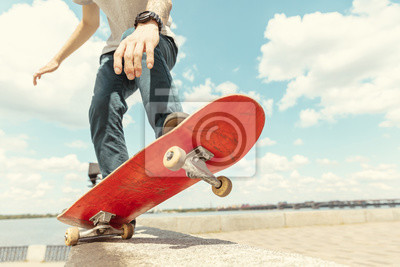 Naklejka Skateboarder doing a trick at the city's street in sunny day. Young man in sneakers and cap riding and longboarding on the asphalt. Concept of leisure activity, sport, extreme, hobby and motion.