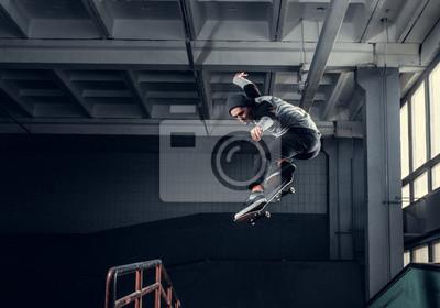 Naklejka Skateboarder jumping high on mini ramp at skate park indoor.