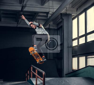 Naklejka Skateboarder performing a trick on mini ramp at skate park indoor.