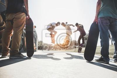 Naklejka Skaters jumping with skateboard in city skate park - Main focus on center guys heads