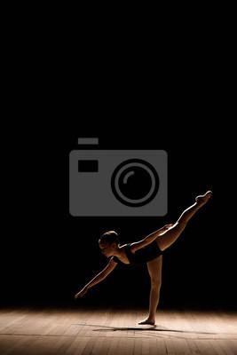 Naklejka Śliczna mała balerina w ciemnym baletniczym kostiumu tanu na scenie. Dziecko w klasie tanecznej. Dziecko dziewczynka studiuje balet.