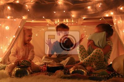 Naklejka Śliczni małe dzieci bawić się z kitchenware podczas gdy siedzący w hovel w domu