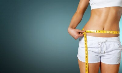 Naklejka Slim young woman measuring her thin waist with a tape measure