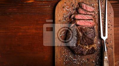 Naklejka smaczny i świeży, bardzo soczysty stek wstążkowy z marmurkowej wołowiny na drewnianym stole.