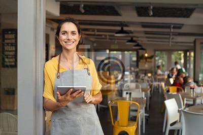 Naklejka Small business owner at entrance looking at camera