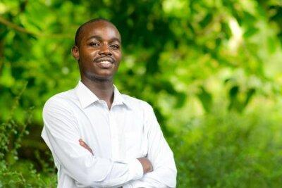 Naklejka Smile african portrait man in green nature background.