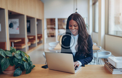 Naklejka Smiling African American businesswoman using her laptop at a tab