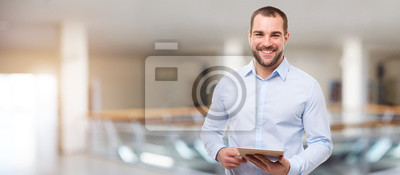 Naklejka Smiling business man in the business center with tablet
