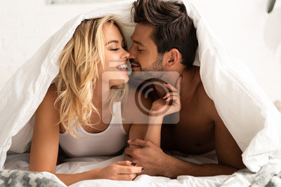 Naklejka smiling couple going to kiss under sleeping sheets in the morning