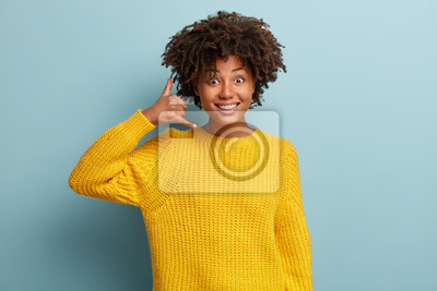 Naklejka Smiling delighted black woman makes phone gesture, shows call me back sign with hand near ear, pretends talking on mobile phone, dressed in yellow clothes, has glad expression, poses indoor.