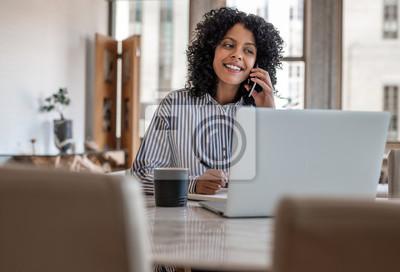 Naklejka Smiling female entrepreneur sitting at home talking on her cellphone