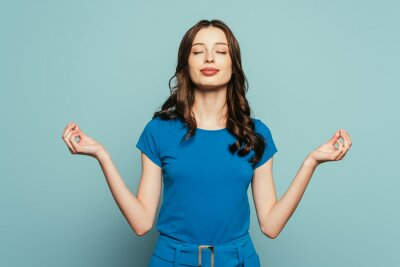 Naklejka smiling girl standing in meditation pose with closed eyes on blue background