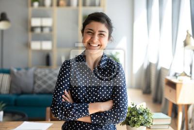 Naklejka Smiling indian woman looking at camera posing at modern home