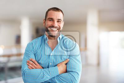 Naklejka Smiling man standing in business center