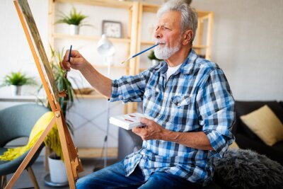 Naklejka Smiling mature man painting on canvas at home